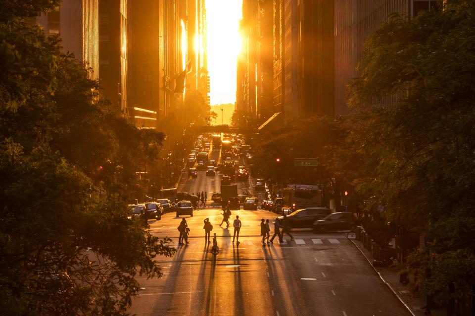 Rays of sunlight shining down on the people and traffic at the intersections along 42nd Street in New York City